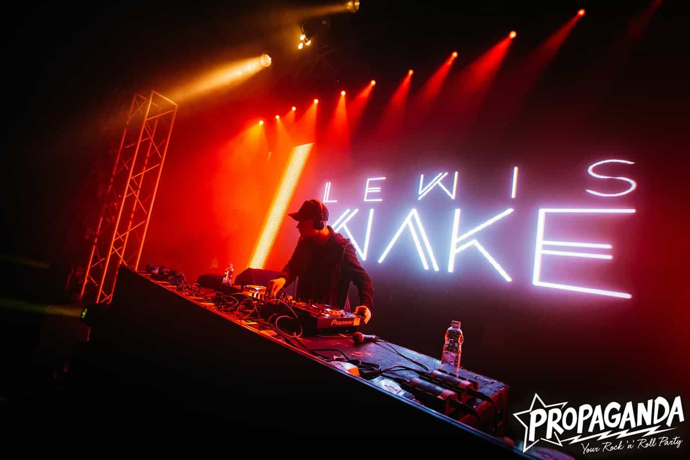 Image of Lewis Wake DJing with his name in lights behind him